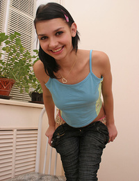 Startling brunette with a seductive look is sitting on the white chair in the kitchen in blue tank-top and jeans, which she slowly takes off.